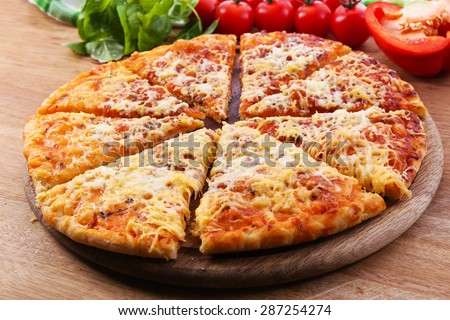 Cheese pizza on wooden cutting board, closeup - stock photo