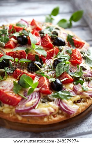 Cheese pizza with cherry tomatoes, red onion and capers (topped with arugula and basil) - stock photo