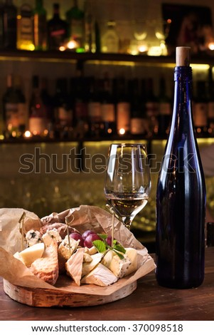 Cheese plate and glass of wine - stock photo
