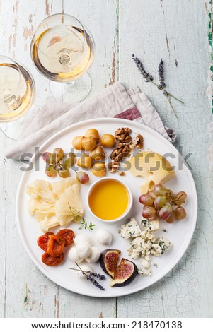 Cheese plate Assortment of various types of cheese and honey on white plate - stock photo