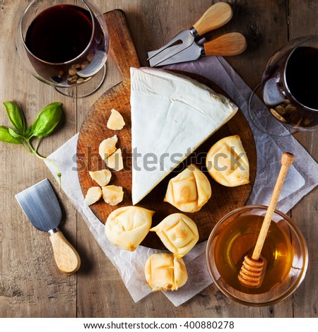 Cheese plate Assortment of various types of cheese and honey on wooden cutting board