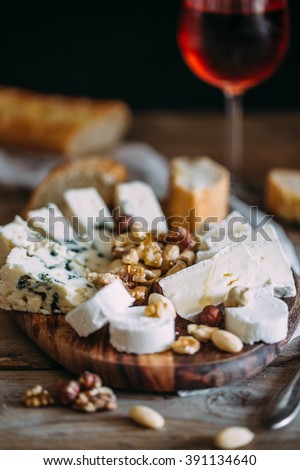 Cheese plate: Emmental, Camembert cheese, blue cheese, bread sticks, walnuts, hazelnuts, honey on wooden table - stock photo