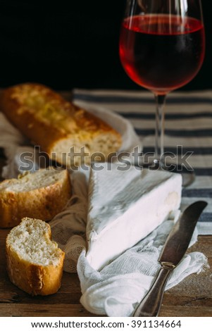 Cheese plate: Emmental, Camembert cheese, blue cheese, bread sticks, walnuts, hazelnuts, honey on wooden table