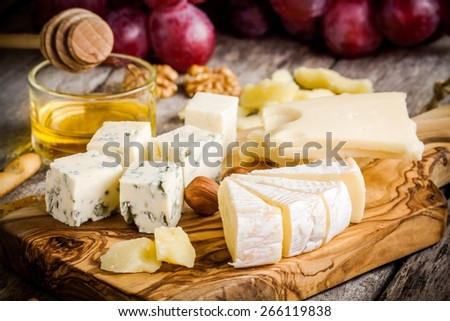 Cheese plate:Emmental, Camembert, Parmesan, blue cheese, bread sticks, walnuts, hazelnuts, honey, grapes - stock photo