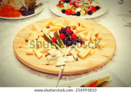 Cheese plate in a restaurant decorated with fruit - stock photo