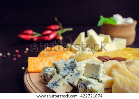 Cheese plate: Parmesan, cheddar, gouda, blue cheese, mozzarella and other with chili pepper and almonds on wooden board. Tasty appetizers. Cheese platter. Cheese board. Cheese slice. Selective focus. - stock photo