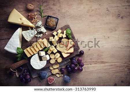 Cheese plate served with grapes, jam, figs, crackers and nuts on a wooden background - stock photo