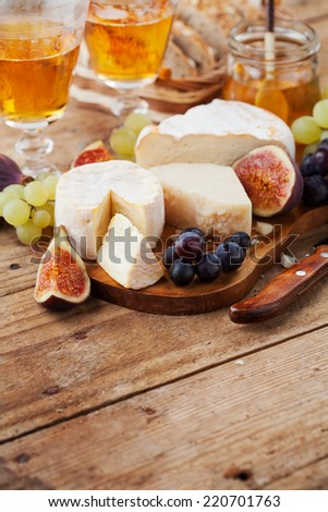 Cheese plate. Variety of cheese sorts with grapes and figs