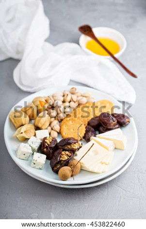 Cheese plate with assorted cheese and crackers, dates and nuts - stock photo