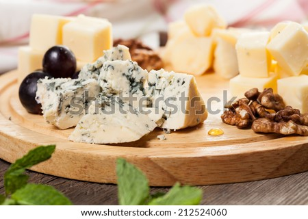 Cheese plate with cheeses Dorblu, Parmesan, Brie, Camembert and Roquefort in serving on the table from an old tree close-up - stock photo