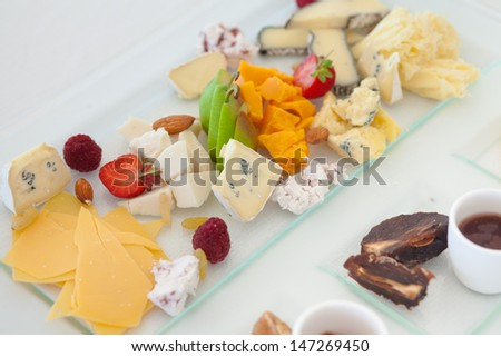 Cheese plate with fruits and sauce on restaurant table - stock photo