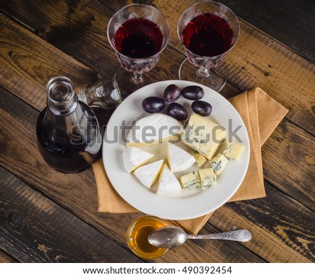 Cheese plate with grape and wine on wood