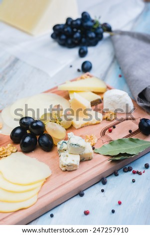 cheese plate with grapes on the wooden table - stock photo