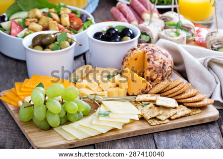 Cheese plate with variety of appetizers on table - stock photo