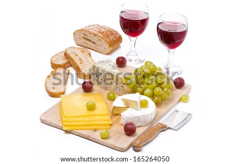 Cheese platter, grapes, bread and two glasses of red wine, isolated on white