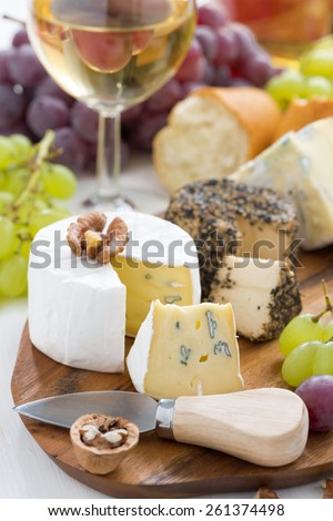 cheese platter, snacks, bread and wine on wooden board, vertical, close-up