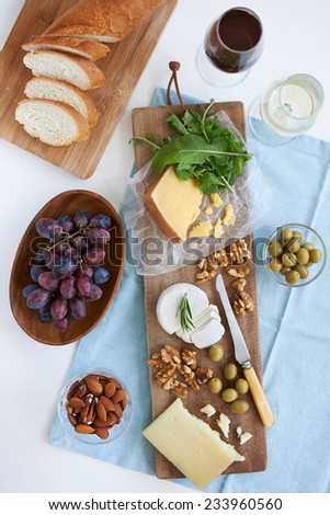 Cheese platter starter appetiser pre-dinner snack, assortment of different cheeses, nuts, olives and grapes served with wine - stock photo