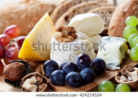 Cheese platter: variety of cheeses on wooden plate with fruits and bread - stock photo