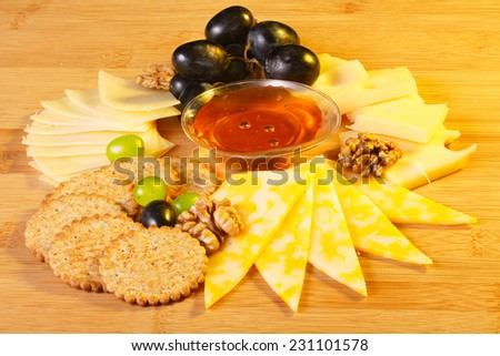 Cheese platter. Various kinds of cheese with grape and honey - stock photo