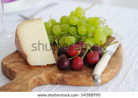 Cheese platter with tom goat cheese and fruits. Cheeseboard