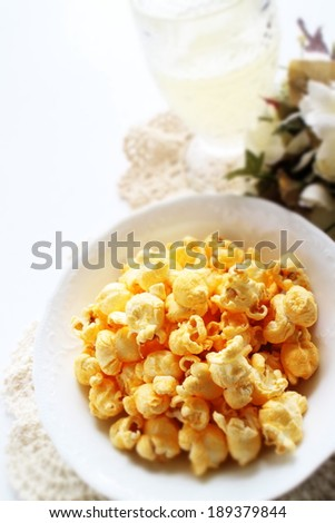 Cheese popcorn on white bowl with iced drink on background - stock photo