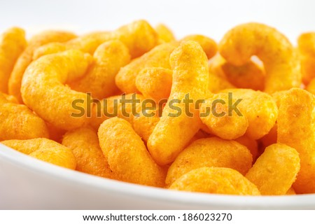 Cheese puff snacks on bowl closeup  - stock photo