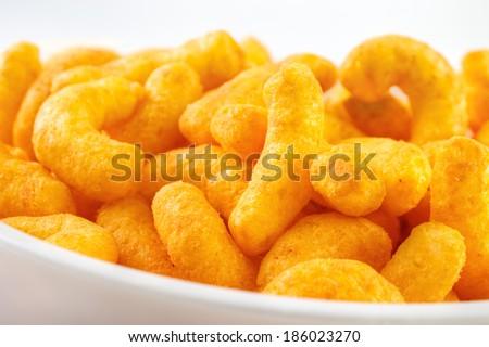 Cheese puff snacks on bowl closeup  - stock photo