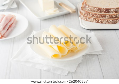 cheese rolled up on white plate with bread and cold cuts at the background