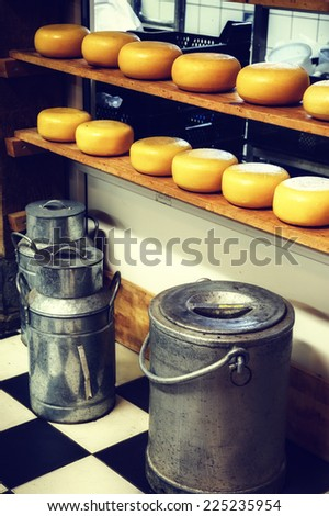 Cheese rounds and milk cans in small dairy factory - stock photo