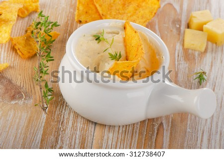 Cheese Sauce with Nachos on  wooden table. Selective focus