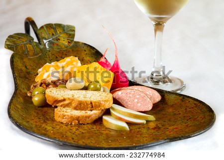 Cheese, Sausage, and Olives on a pear shaped platter - stock photo