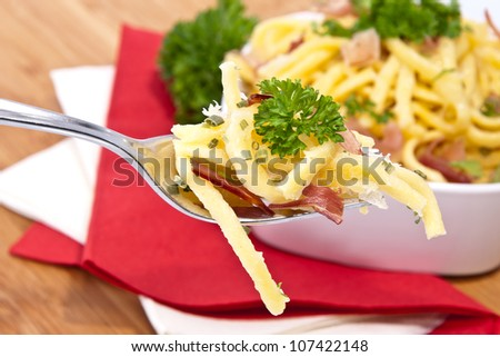 Cheese Spaetzle in a bowl with portion on fork (on wooden background) - stock photo