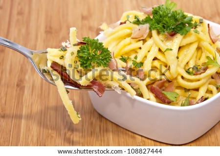 Cheese Spaetzle with portion on fork on wooden background