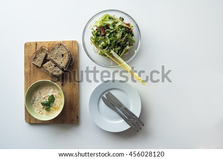 Cheese spread & baked bread with fresh summer salad. Flat lay food on white wooden table. - stock photo