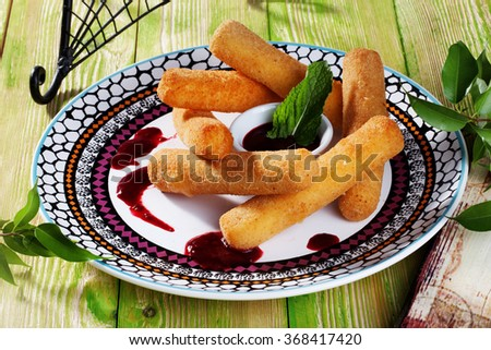 cheese sticks with breaded mint cranberry sauce, still life beautiful, wooden table, Provence, the menu, close-up food - stock photo