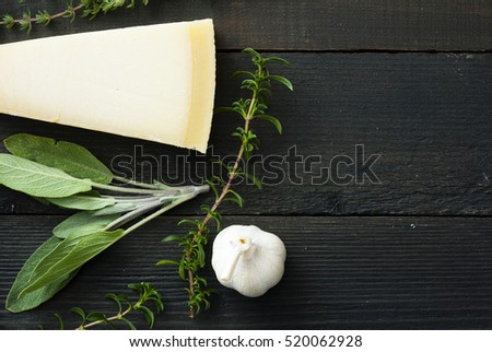 cheese, tomatoes, and fresh herbs on black wood table background