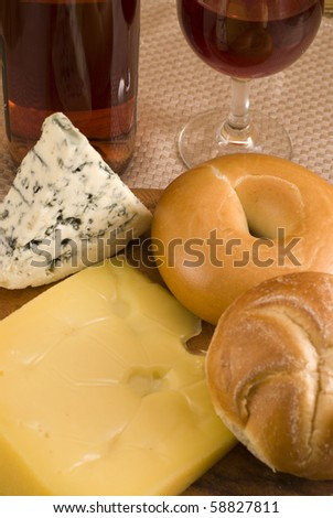 Cheese variates , bagel, roll and glass of wine