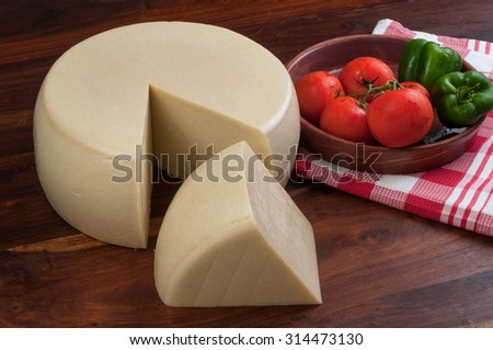Cheese wheel  and a piece on wooden background decorated with table cloth tomatoes and green peppers. - stock photo