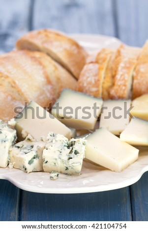 cheese with bread on white dish on blue wooden background