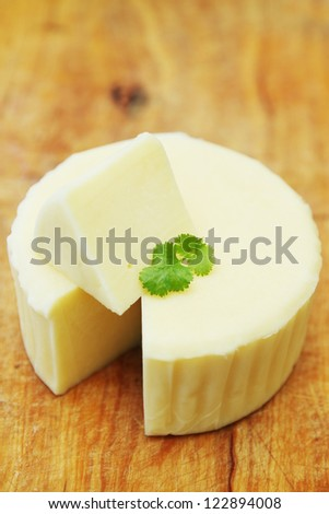 Cheese with coriander leaves on a wooden board