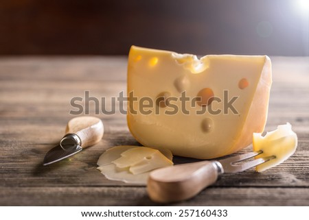 Cheese with fork and knife on rustic wooden background