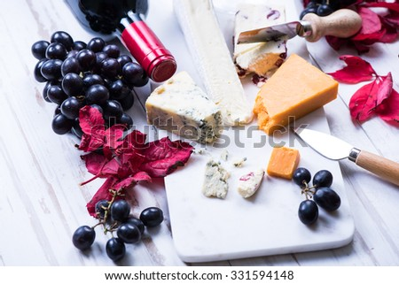cheese with grapes and wine and autumn leaves - stock photo