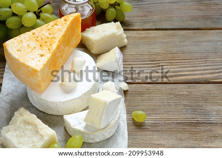 cheese with grapes on wooden background, food closeup