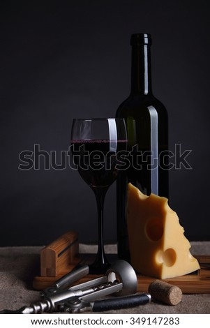 Cheese with holes and a glass of wine.