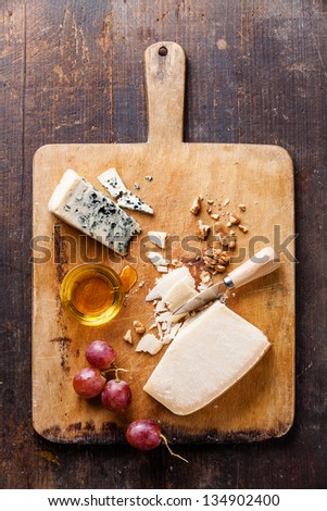 Cheese with honey, nuts and grapes on wooden cutting Board - stock photo