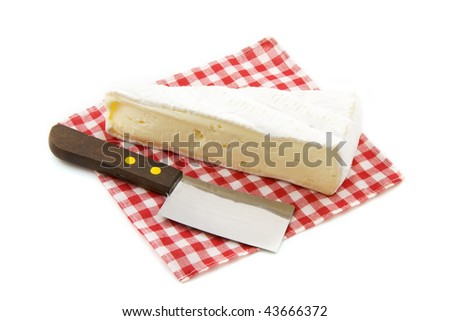 Cheese with knife on a blocked napkin isolated over white - stock photo