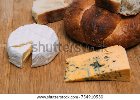 Cheese with mold and camembert with bread on a wooden surface, traditional Italian food.