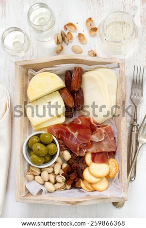 cheese with prosciutto, cookies, olives and wine - stock photo
