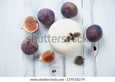 Cheese with ripe figs, white wooden background, above view - stock photo