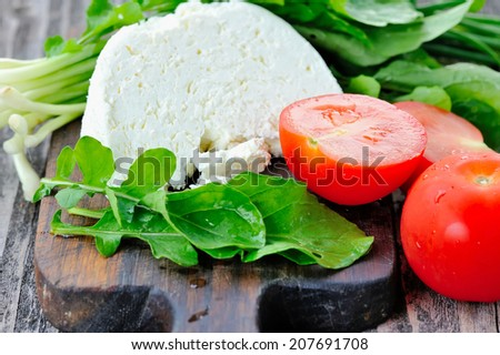 Cheese with tomatoes and arugula and onion on a wooden board - stock photo